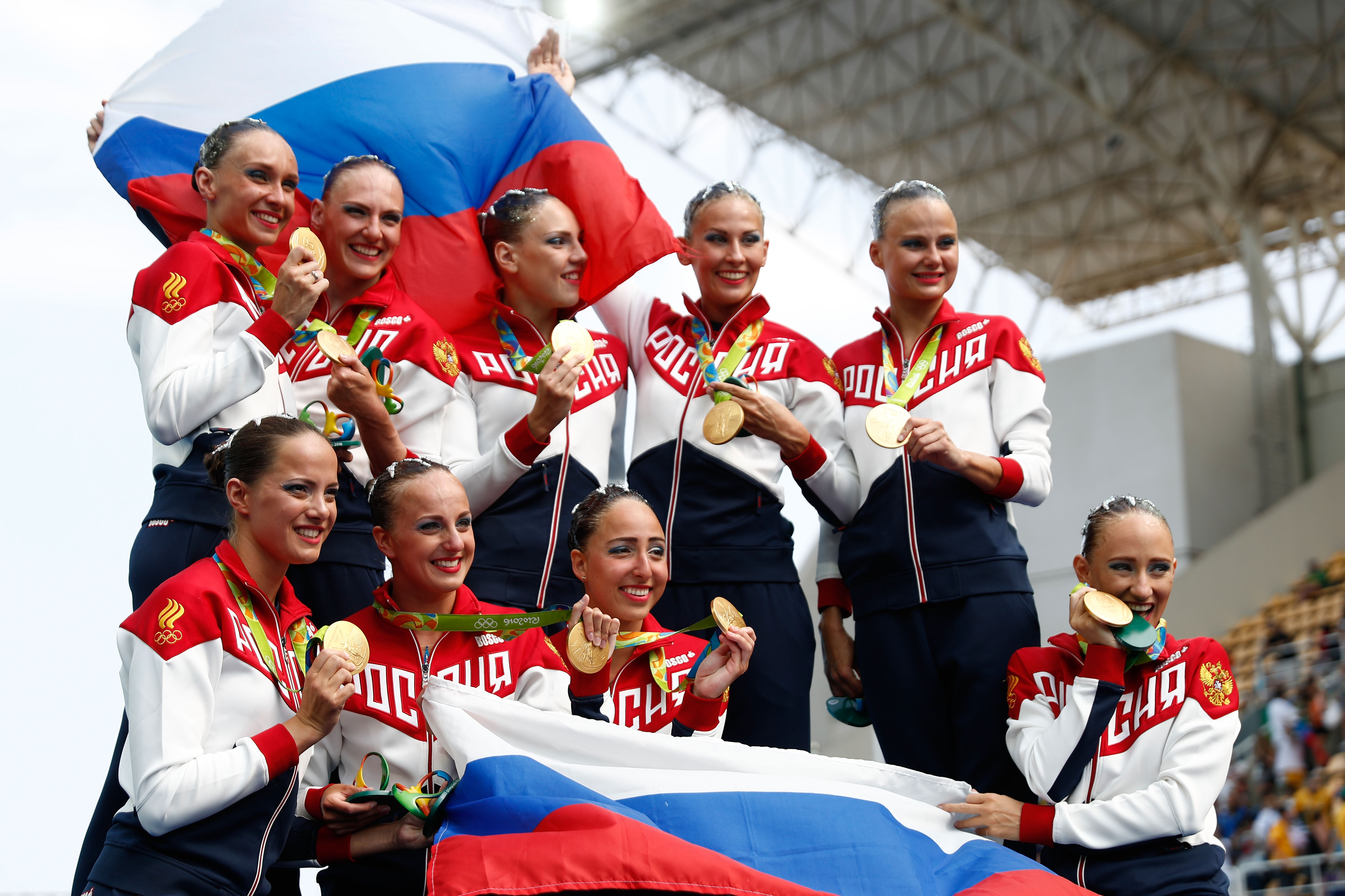 RIO DE JANEIRO, BRAZIL - AUGUST 19: Team Russia celebrates winning gold on the podium during the medal ceremony for the Synchronised Swimming Teams Free Routine on Day 14 of the Rio 2016 Olympic Games at the Maria Lenk Aquatics Centre on August 19, 2016 in Rio de Janeiro, Brazil. (Photo by Clive Rose/Getty Images)