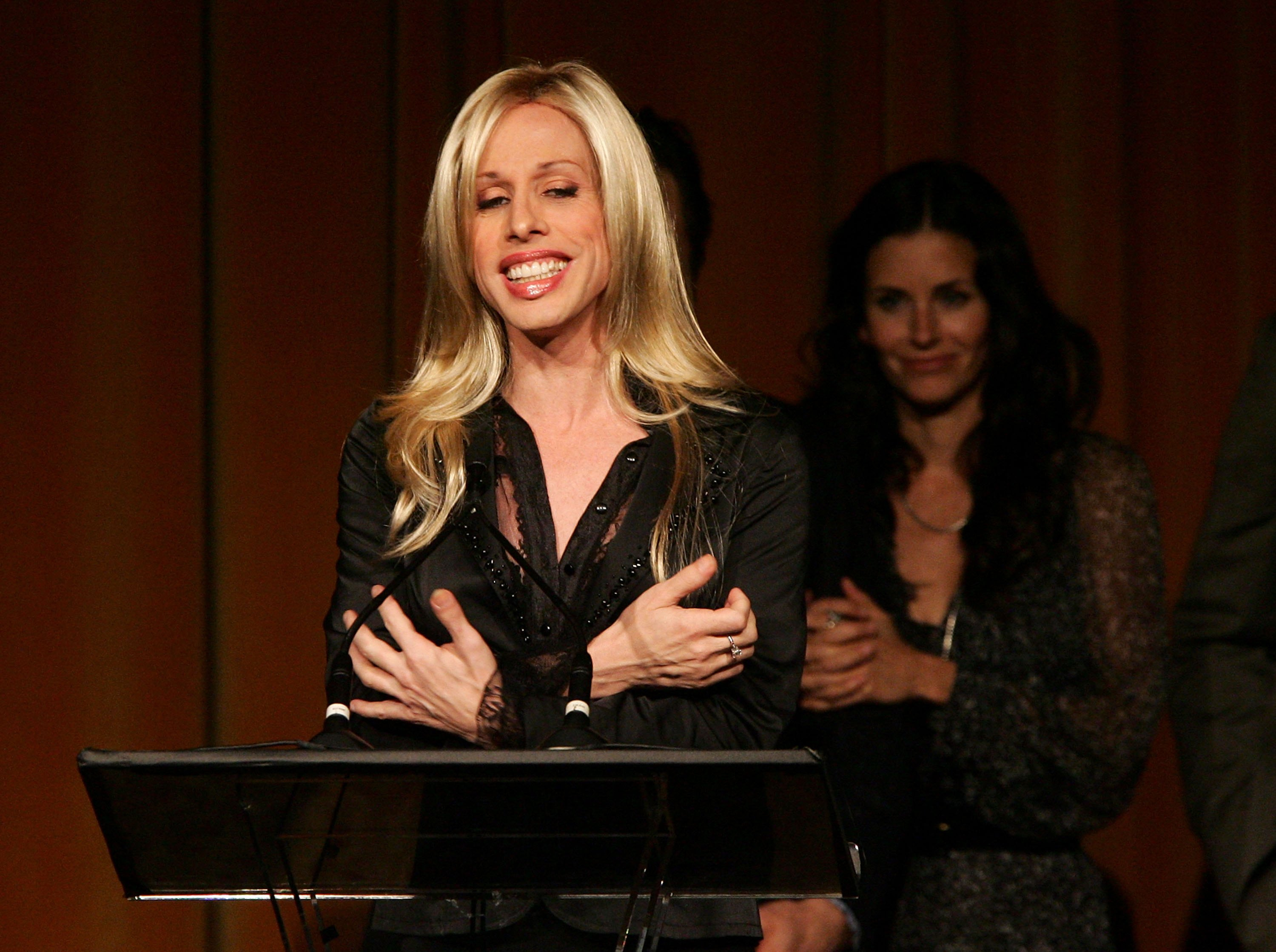 "BEVERLY HILLS, CA - MAY 10: Actress Alexis Arquette accepts the ""Platinum Circle Award"" onstage with David Arquette, Courteney Cox Arquette and Thomas Jane in the background at the AFI Associates luncheon honoring Hollywood's Arquette family with the 6th Annual ""Platinum Circle Award"" held at the Regent Beverly Wilshire Hotel on May 10, 2006 in Beverly Hills, California. (Photo by Frazer Harrison/Getty Images for AFI)"