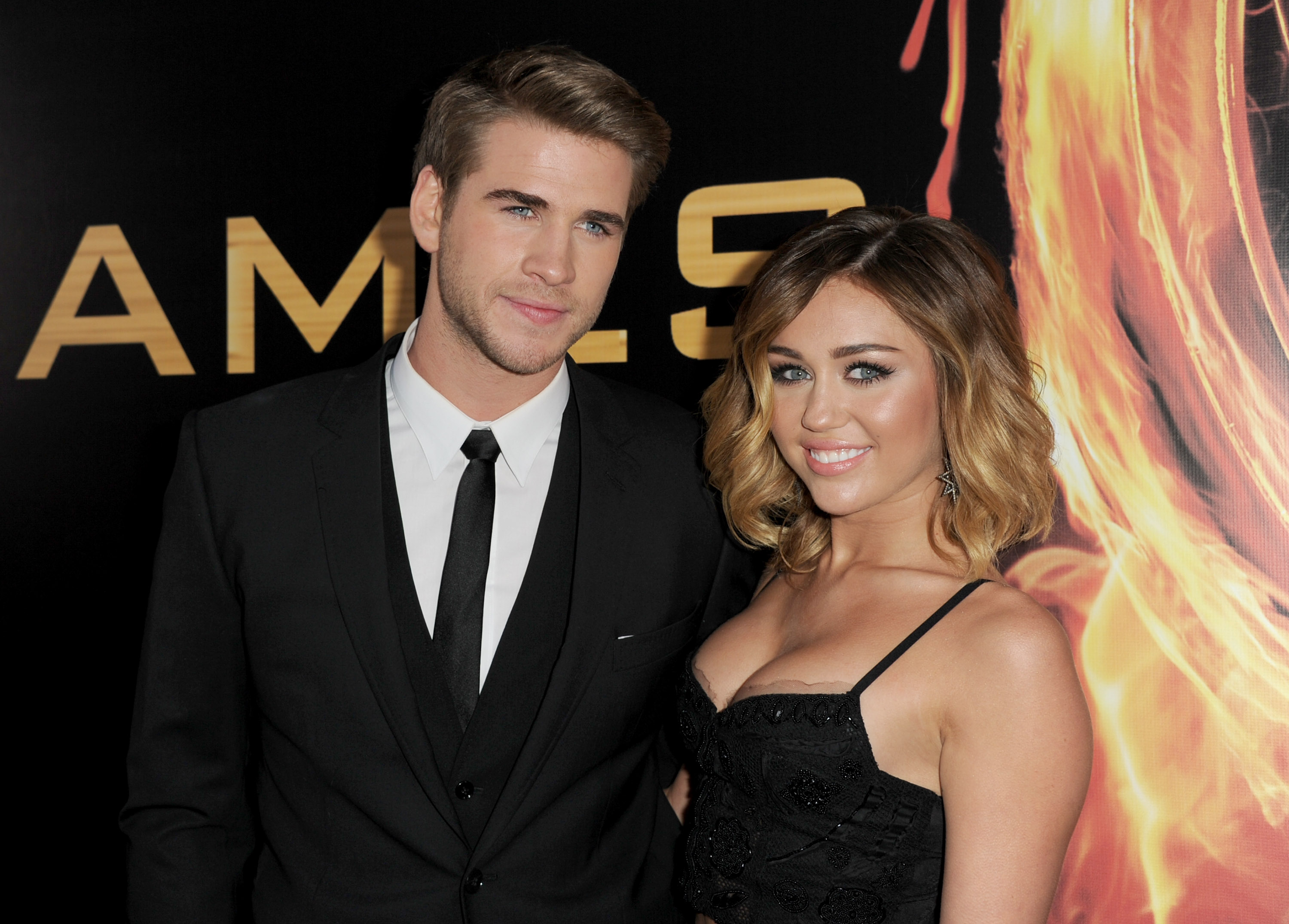 "LOS ANGELES, CA - MARCH 12:  Actor Liam Hemsworth (L) and singer Miley Cyrus arrive at the premiere of Lionsgate's ""The Hunger Games"" at Nokia Theatre L.A. Live on March 12, 2012 in Los Angeles, California.  (Photo by Kevin Winter/Getty Images)"