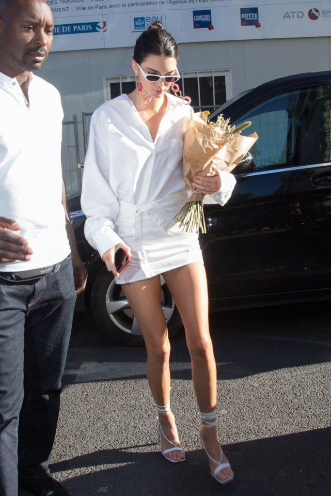 Еще один total white образ от Кендалл Дженнер: белая рубашка + белая мини-юбка и босоножки с перепонкой в тон. Идеально, когда в городе жара!