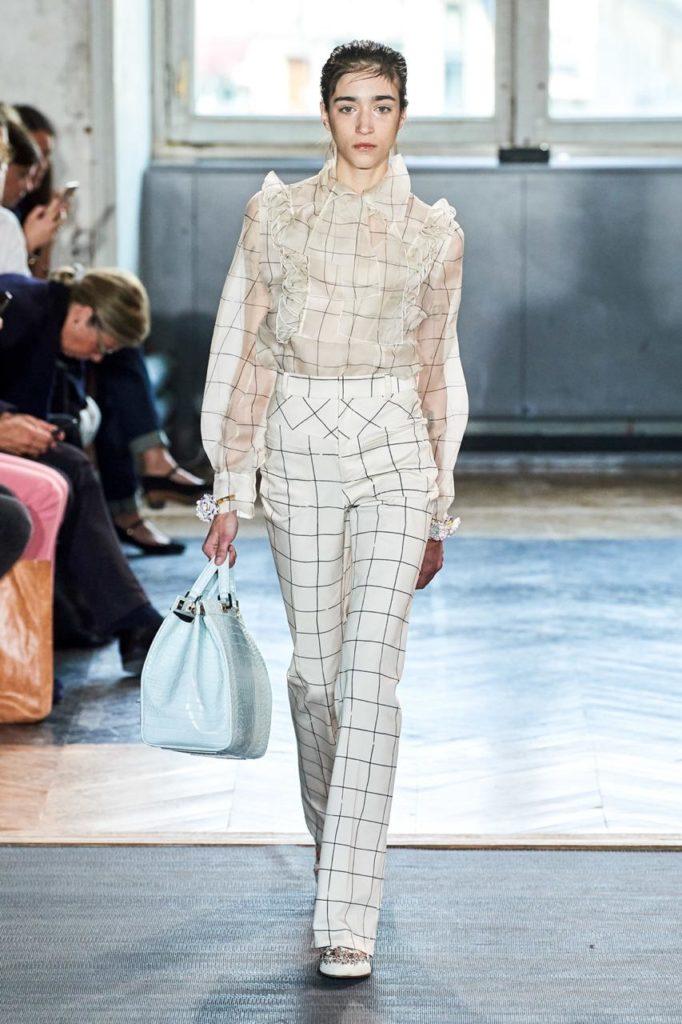 Носи брюки в клетку с полупрозрачной рубашкой и большой сумкой